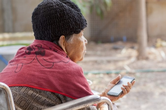Old Woman Staring ahead and holding cell phone
