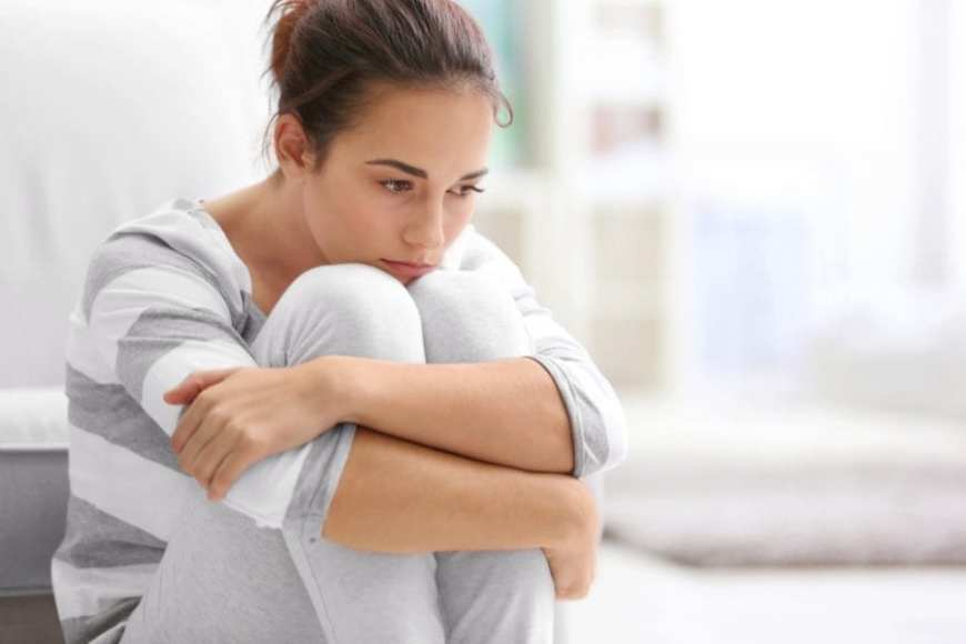 Anxious Young Woman Sitting on bed holding her knees