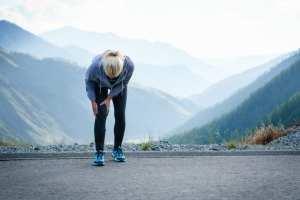 Arthritis in the knee of female runner as she hunches over
