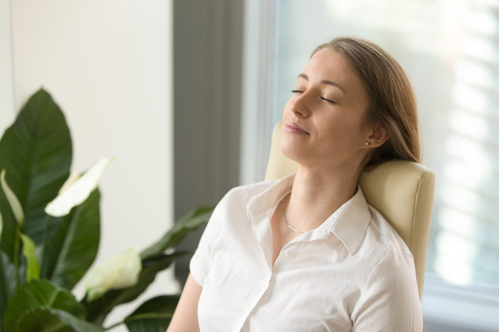 good mental wellness represented by young woman leaning back in chair eyes shut and happy