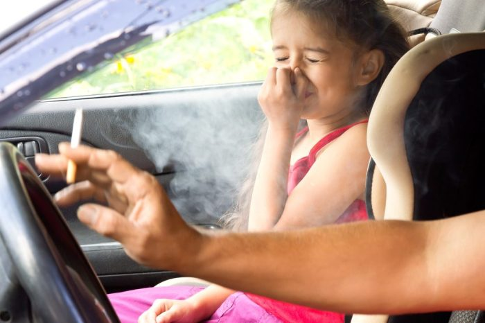 child coughing from cigarette smoke
