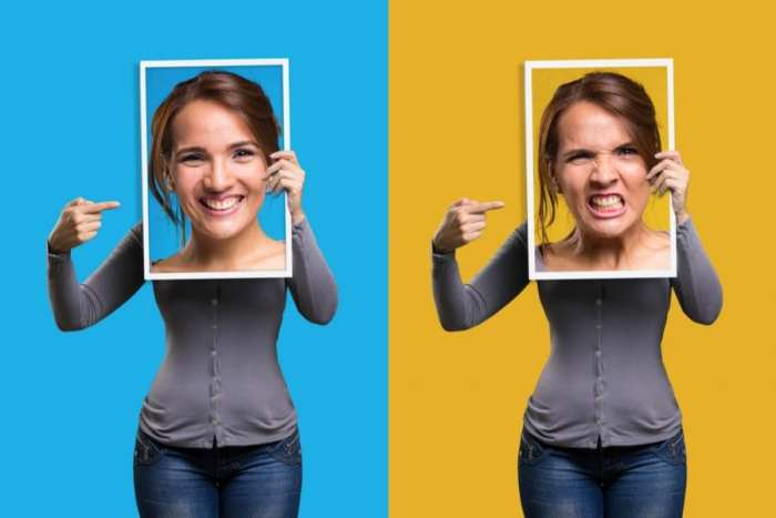 woman holding up happy face versus made face