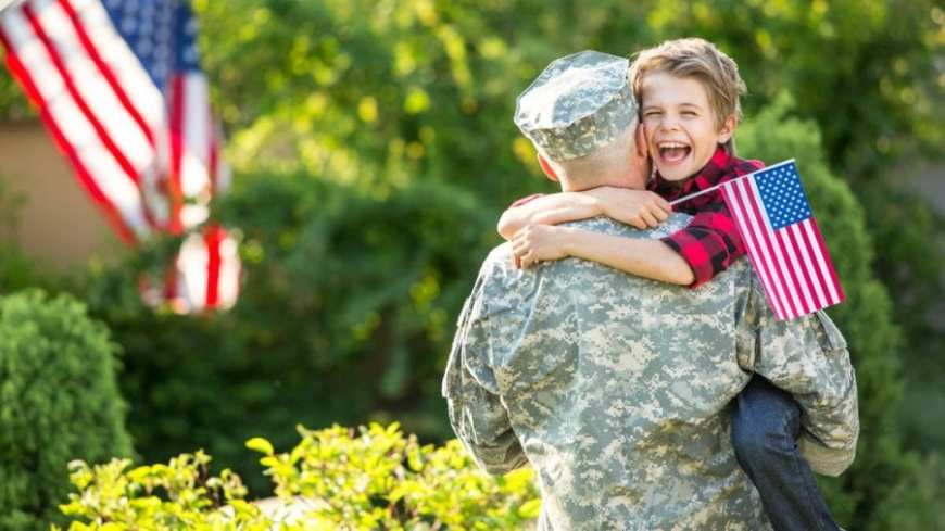 Soldier being embraced by very happy 8 year old son, VA
