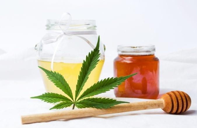 Cannabis Honey in a jar next to cannabis leaves