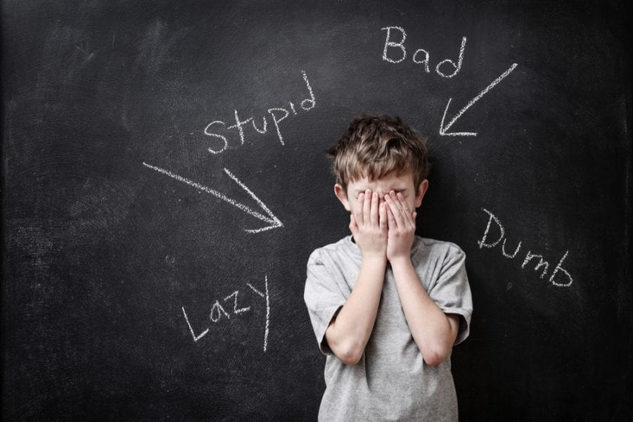 Boy with bad words pointing at him: stupid, lazy, dumb