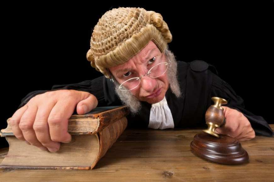 Judge satirical leaning into camera and looking stern