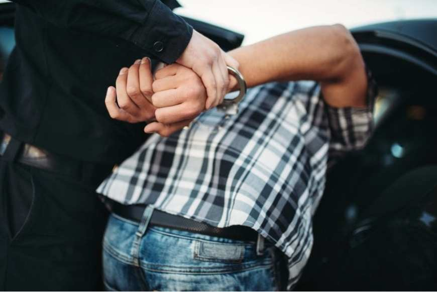 young man handcuffed and shoved into police cruiser