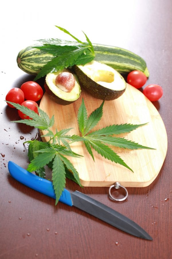 cannabis is a veggie represented by cannabis on cutting board with ovacado and tomatoes