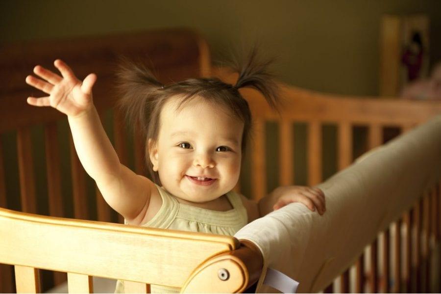 Happy baby waving from crib