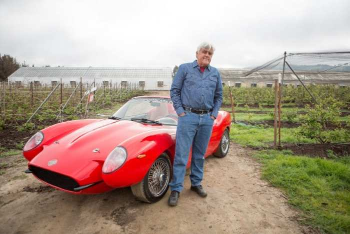 Jay Leno standing in front of his red hemp sports car