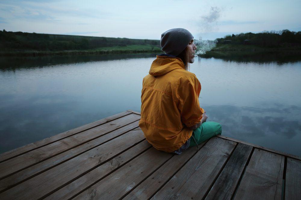 self medicating man on dock near beautiful surroundings in raincoat