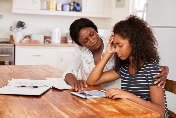 a mother comforts her teen daughter who seems to have anxiety