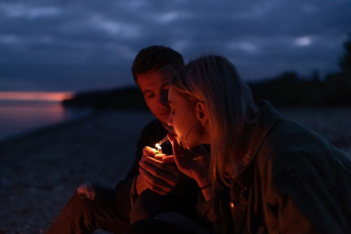 sex and cannabis represented by young couple lighting joint on a beach at night