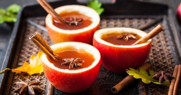 spiced cider in apple glasses with cinnamon sticks