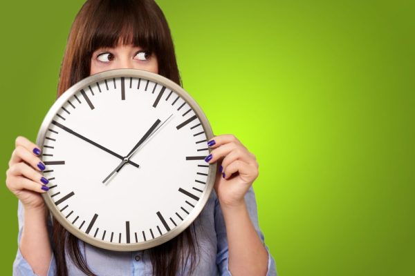 how long do edibles last represented by nervous girl hiding behind clock