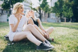 define potent represented by two young women smoking outside on grass