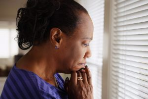 mental health and isolation represented by older african american woman looking nervously out window blinds