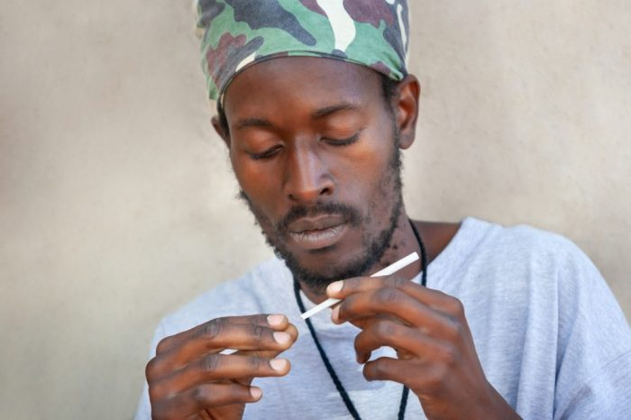 rastafarian man in jamaica looking at a joint