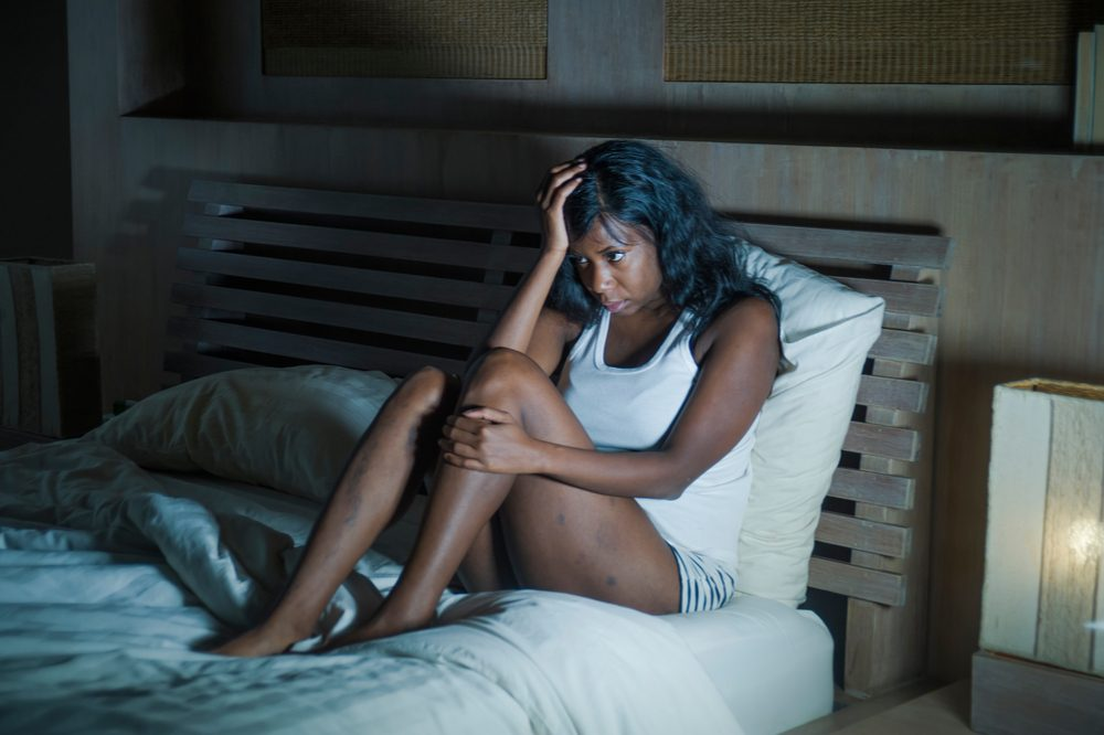 can cbd oil cause nightmares represented by african american woman up in bed holding her head