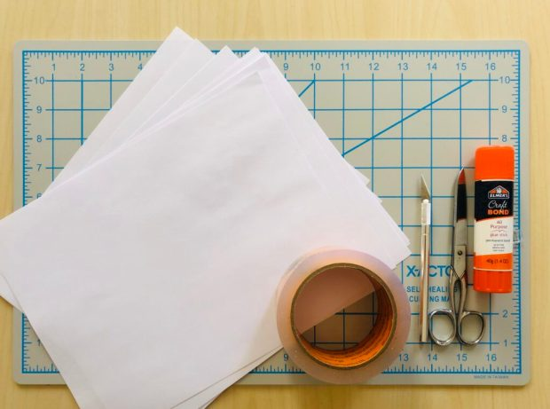 Gather your materials - image of a cutting mat (cardboard also works) transparent tape, a glue stick(bond version), a pair of scissors, an X-Acto knife and some regular printing paper.
