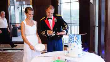Cutting wedding cake with military saber