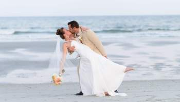 Dipping bride back for a kiss in front of the ocean