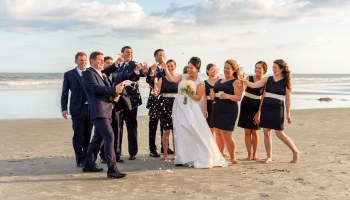 Bridal party opening a champagne bottle together on the beach