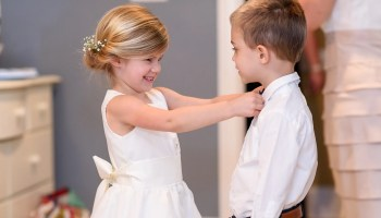 Flowergirl helping the ring bearer with his tie Pawleys Plantation