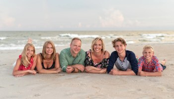 Happy family of 6 laying in the sand together - Huntington Beach State Park