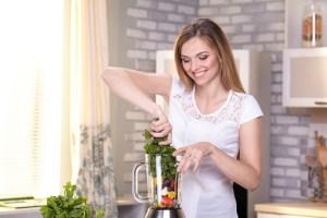 野菜果物ミキサーを扱う白人女性