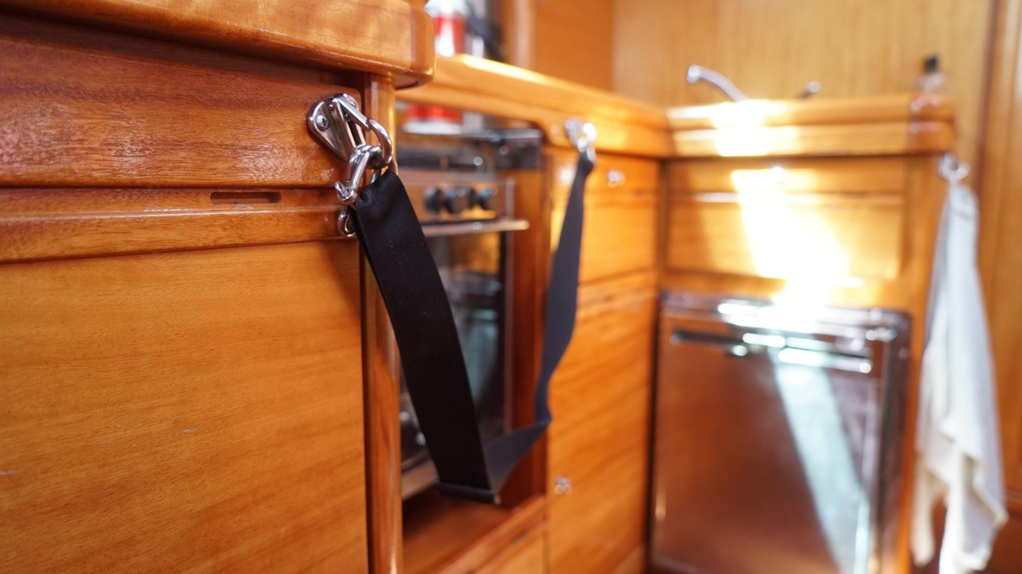 Turvavyölle on kolme kiinnityspistettä. Itsensä voi köyttää niin tiskaamaan kuin hellankin viereen. Huono puoli on, että noihin koukkuihin törmäilee, vaikkei kokkihommissa olekkaan. Atlantin ylityksen jälkeen oli hienoja mustelmia lonkissa.