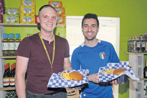 Two medical students showing their gourmet burgers and fries.
