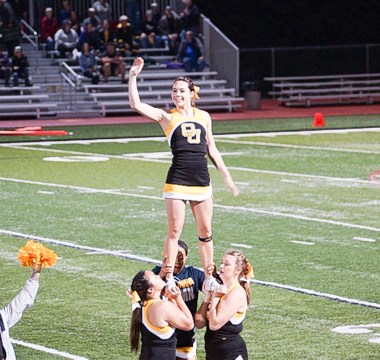 Nicole Brey waves to the crowd while stunting with her Ottawa Braves cheer teammates at a college football game.