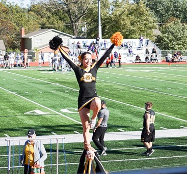 Nicole Brey poses with pom poms in hand as she's held in the air during a college football game with the Ottawa Braves.