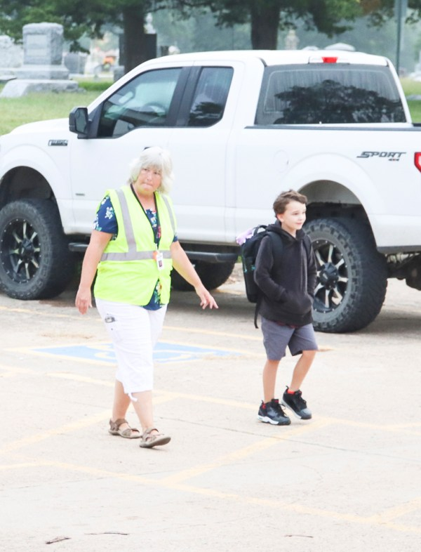 Susan Chandler helps Oliver Byrd across the crosswalk on the first day of school on Thursday, August 19.