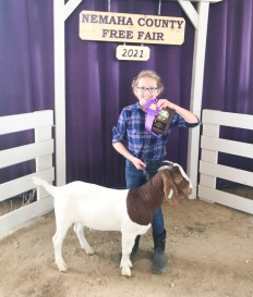 Sydney Aberle stands with her Grand Champion Market Goat at the Nemaha County Fair.
