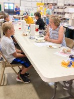 Isaac Schmid gets one of his food projects judged at the Nemaha County Fair.