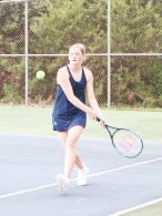 Freshman Audrey Tramp rushes forward to hit the ball during the tennis meet on Monday, September 20.