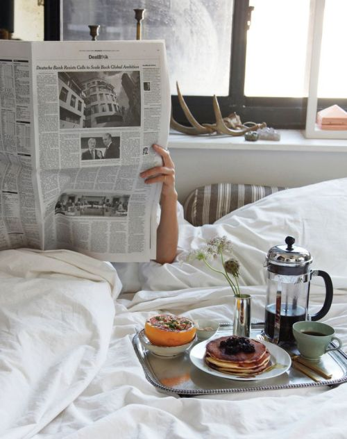 reading newspaper in bed with breakfast