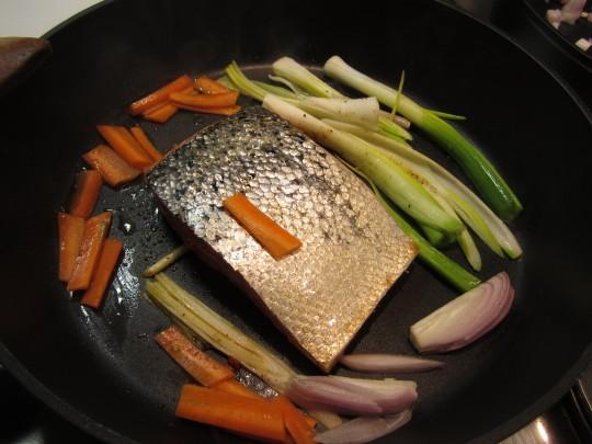Lachs mit Grünzeug und Möhren zuerst auf der hautlosen Seite anbraten.