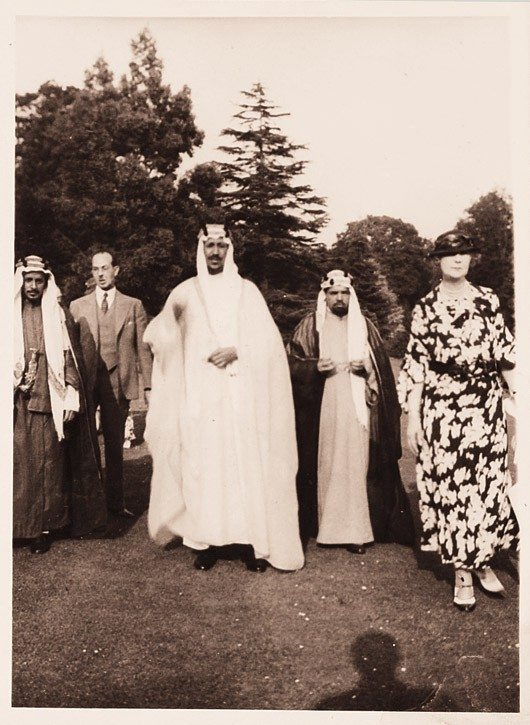 Prince Sa'ud ibn 'Abd al-'Aziz in the centre, Hafiz Wahba stands on the left and slightly behind the prince, Lady Evelyn stands to his left.