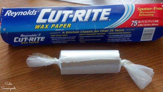 Wrapping a lint fire starter with wax paper for emergency prepping