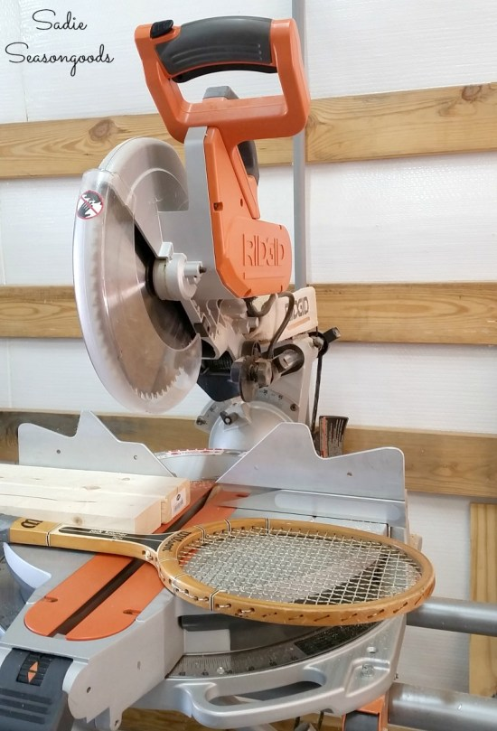 Cutting off the head of a wooden tennis racket for upcycling ideas and Christmas cross stitch