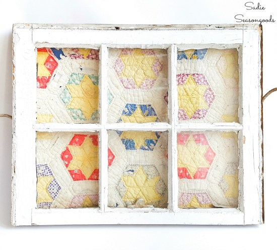 Quilt display in a vintage window for primitive decor