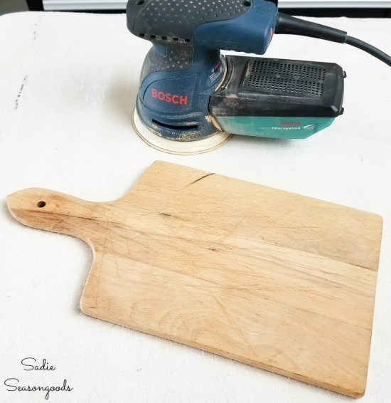 Sanding a cutting board to use as French farmhouse decor
