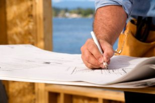 Construction worker making notes on home building plans.
