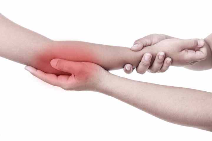Woman's Hand Holding Children's Elbow. Elbow Pain Concept