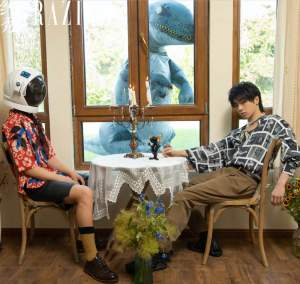 Hua Chenyu Sitting at a table with an astronaut in floral shirt. an inflatable trex looking in through the window