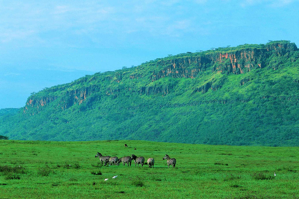 Lake Nakuru National Park landscape includes rocky cliffs and outcrops, stretches of acacia woodland and rocky hillsides.