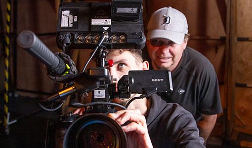 Edoardo Crismani in rear behind the scenes of Deadly Family Portraits: Crombie Crew